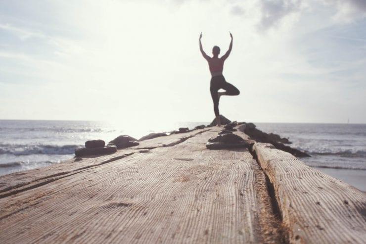Man doing yoga near ocean