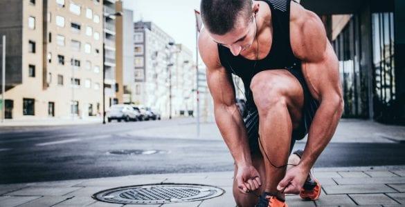 man bent over tying shoe
