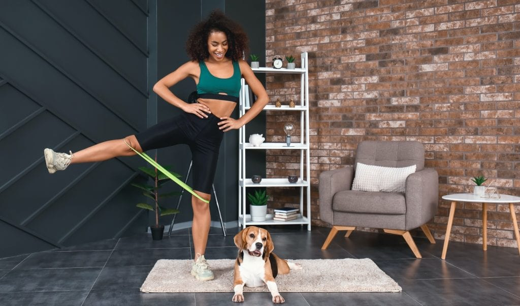woman working out at home with her dog