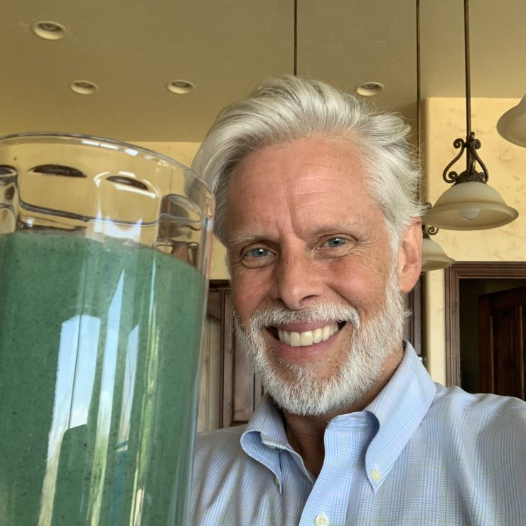 Stan Graham smiling and holding his spirulina drink.