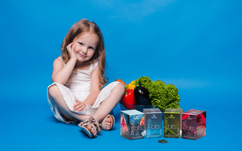 Little girl sitting next to a basket of produce and ENERGYbits mini boxes