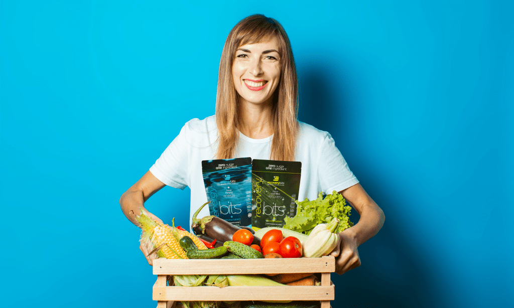 Woman carrying a box of fresh produce and a bag of RECOVERYbits and ENERGYbits