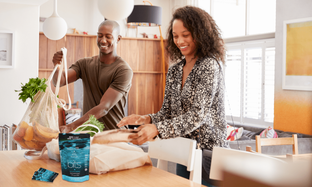 Couple unpacking their groceries with an ENERGYbits bag on the table