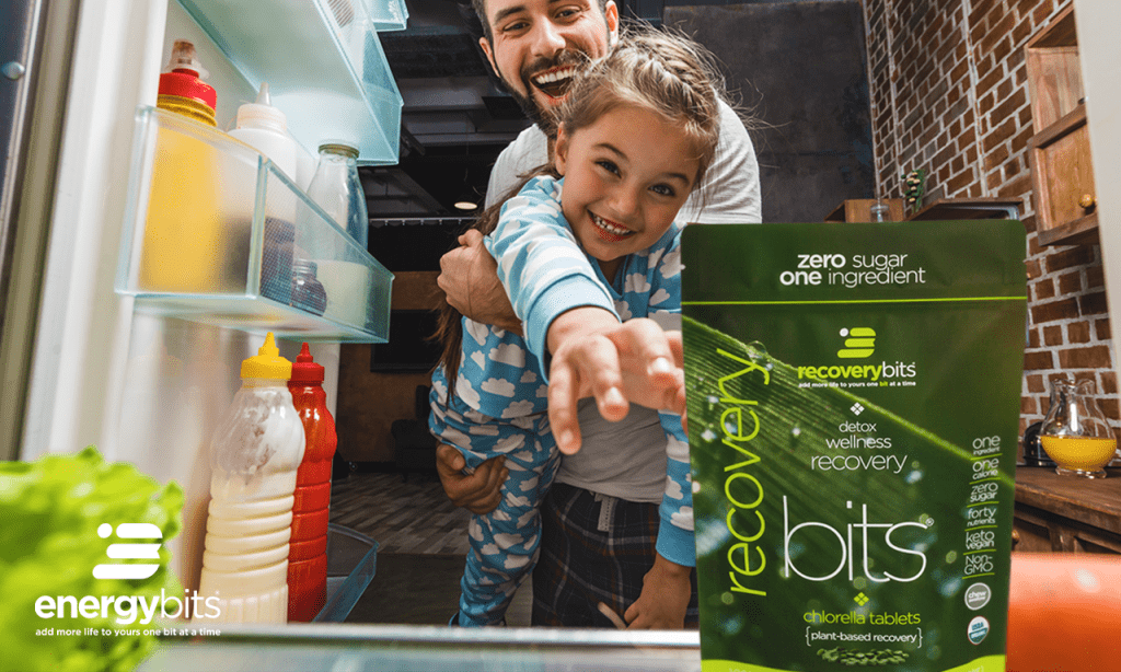 Father and little girl grabbing a bag of RECOVERYbits from the fridge.