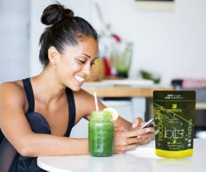 Girl sitting at kitchen table smiling at her phone with a green juice next to her