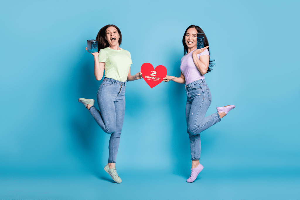 two women jumping with heart