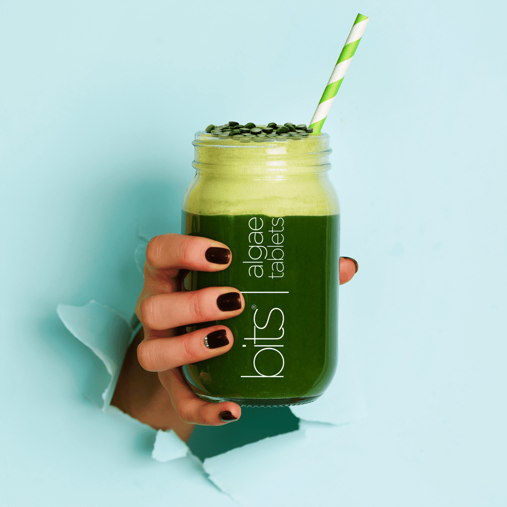 hand holding green smoothie with algae