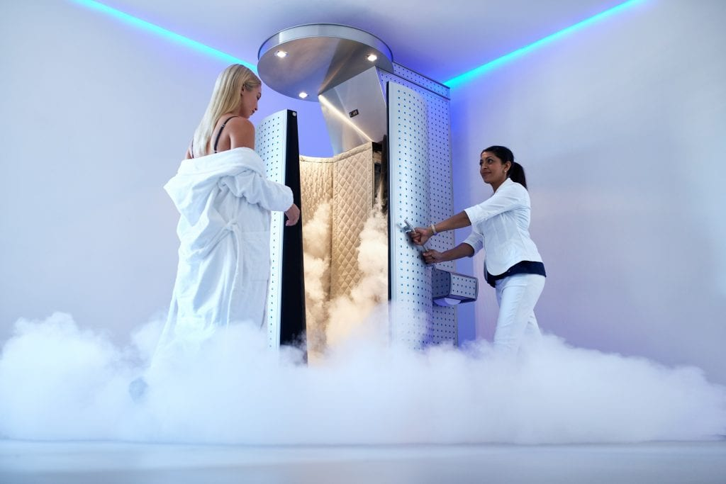 woman going into cryotherapy chamber