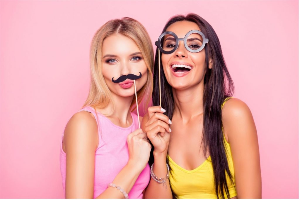 two young woman holding face props
